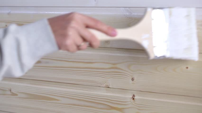 Woman painting wooden slot and key boards in white color with brush