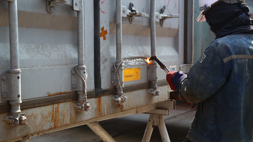 Industrial worker cutting container box by using metal torch. - 4K stock footage clip