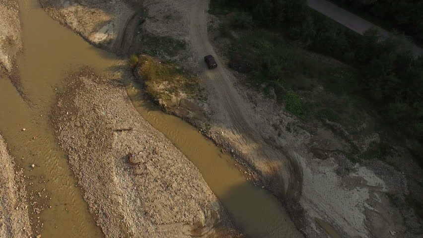 Aerial view over an Off-road vehicle crossing a river in speed.  | Shutterstock HD Video #16395517
