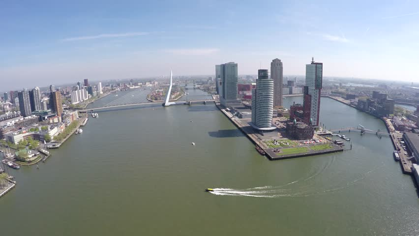 Aerial of Rotterdam city flying towards Erasmus Bridge Erasmusbrug showing business district right boat sailing past cityscape bird view of city center large city in south of Netherlands Holland 4k #16455376