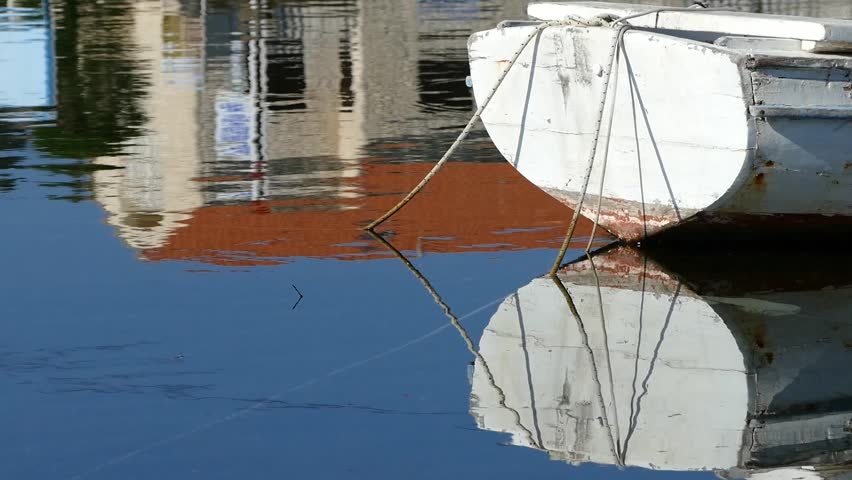 Old wooden boat and reflections on the sea surface - HD stock video clip
