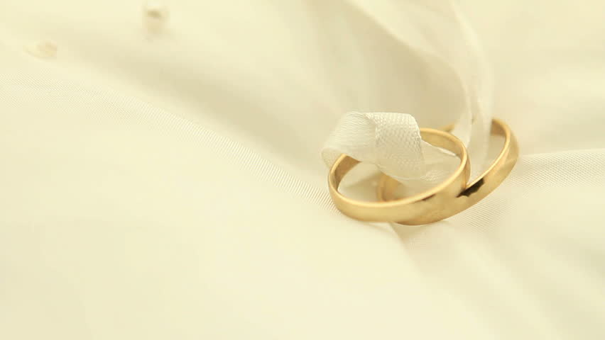 Wedding rings on pillow, turning slowly Pillow is off white - HD stock video clip