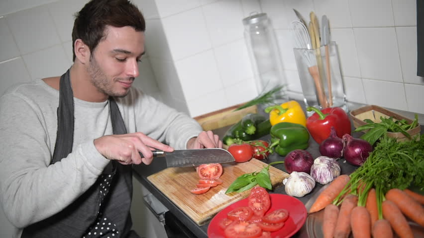 Man chopping vegetables in kitchen and using digital tablet - 4K stock footage clip