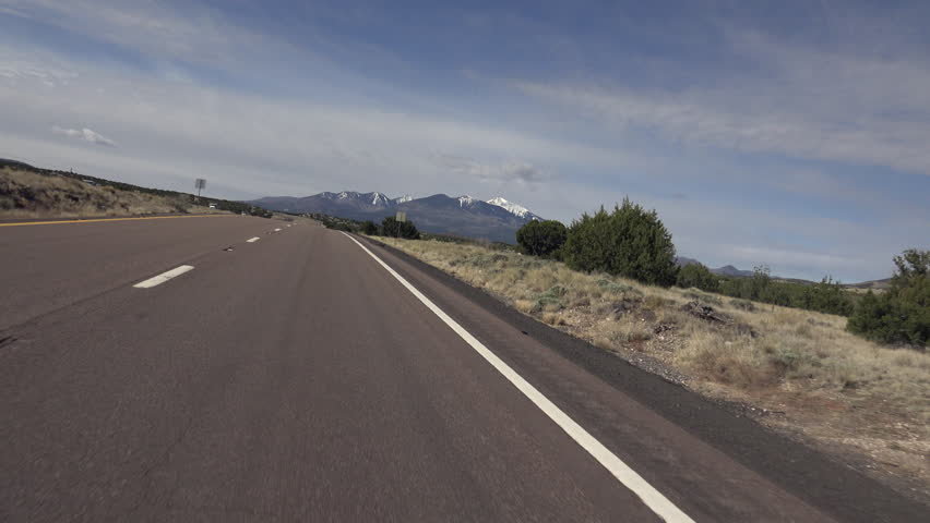 Driver POV, Travel towards snow-capped mountains, blue sky, clouds background. 4K UHD 3840x2160 - 4K stock video clip