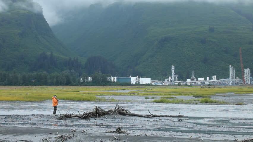 Man fishing for salmon in the rain and fog on a tidal river near oil refinery Valdez, Alaska.  - HD stock video clip