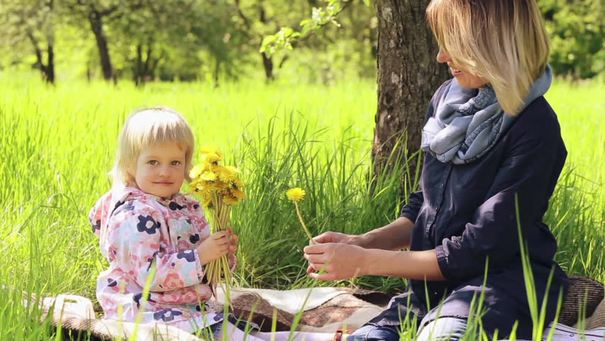 Little girl and young mother enjoying spring field dandelion flowers. Funny child playing with mum in sunny garden or backyard on spring day. Portrait of happy family of two people outside. - HD stock footage clip