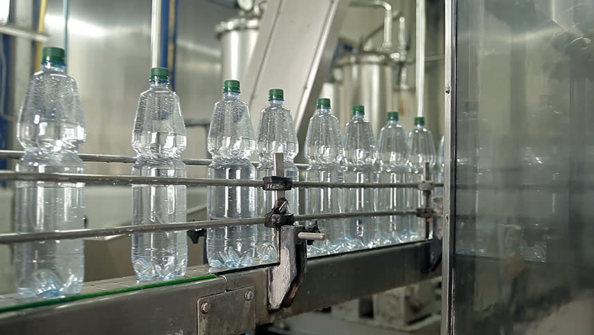 The machine is pouring mineral water into bottles - HD stock footage clip