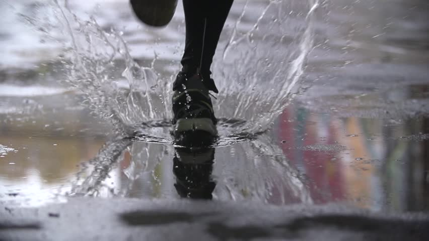 Close up slow motion shot of legs of a runner in sneakers. Male sports man jogging outdoors in a park, stepping into muddy puddle. Single runner running in rain, making splash. | Shutterstock HD Video #16808320