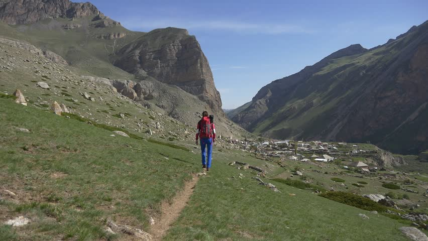 Woman with backpack on the shoulders goes on the trail in the direction of the mountain village