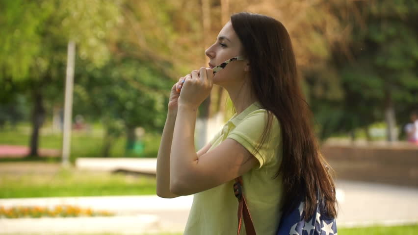 Caucasian girl walking outdoors and stopped to wear sun-glasses. woman relaxing in the park. HD video