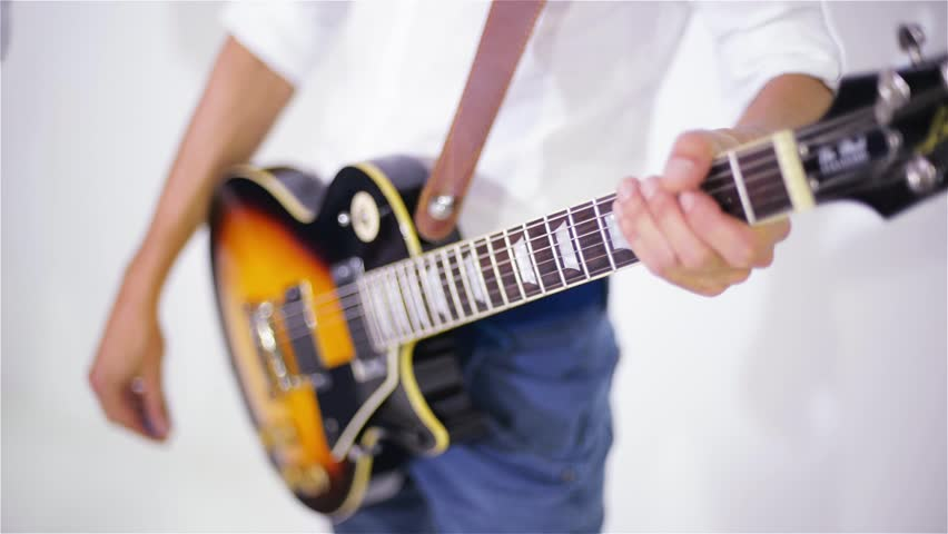 Man playing guitar in the studio on a white background, close-up