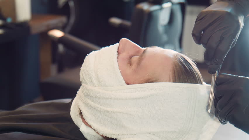 Unrecognizable barber in black gloves wrapping client's beard in hot towel   Shutterstock HD Video #16929028