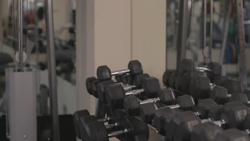 Young fit beautiful girl in gym. Ungraded. Taking dumbbells - HD stock video clip