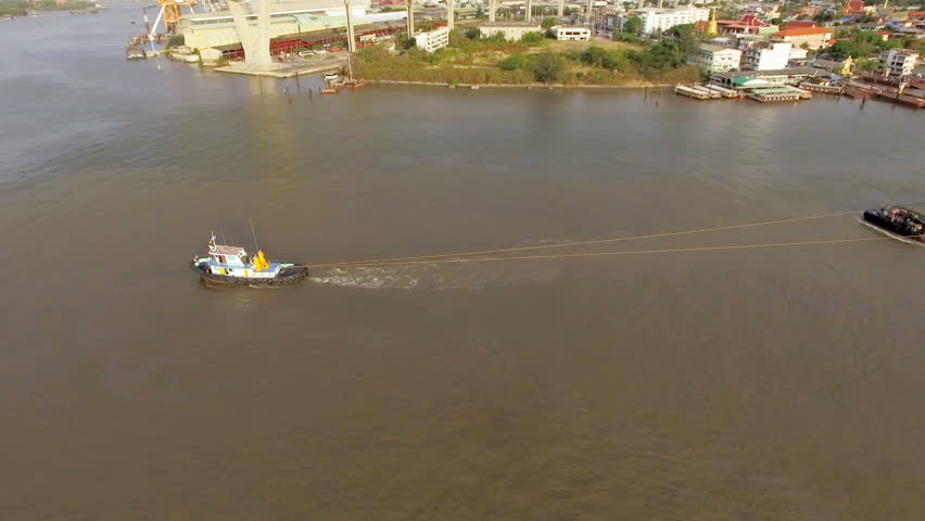 aerial view of tug boat or ship, container transportation ship on chao phraya river, transportation concept, panning camera shot, High quality footage 4K - 4K stock video clip