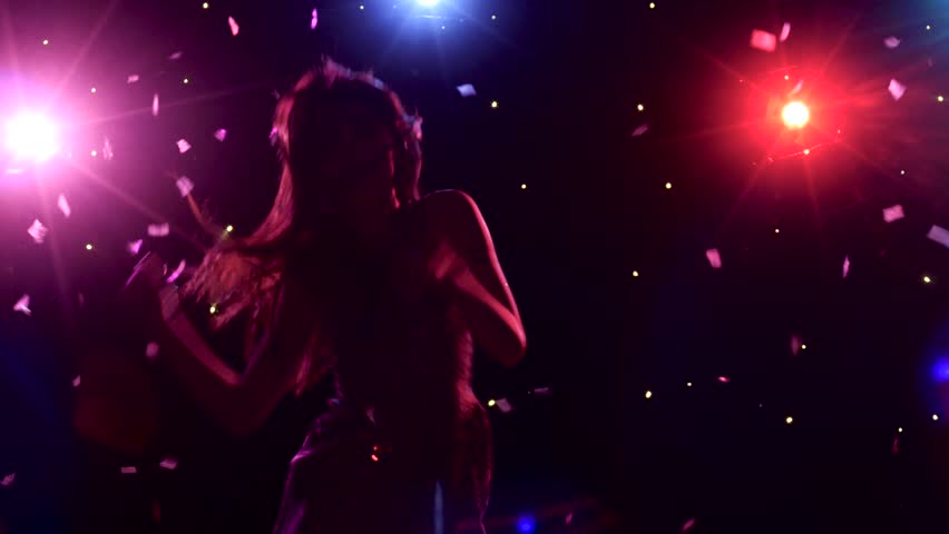 Silhouette of dancing girl with disco style lights and confetti - 4K stock footage clip