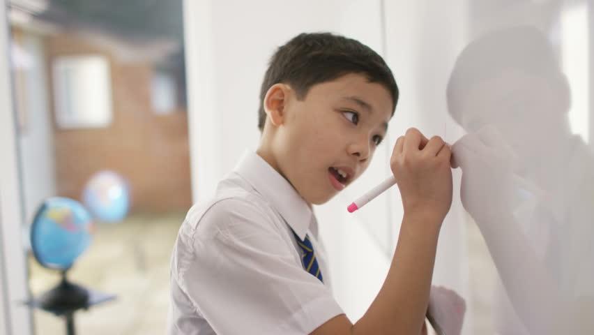 4K Happy school boy in class listening to teacher & writing on whiteboard UK - April, 2016 | Shutterstock HD Video #17024842