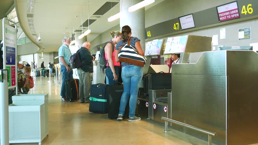 VALENCIA, SPAIN - MAY 28, 2016: Airline passengers checking in at an airline counter in the Valencia Airport. About 4.98 million passengers passed through the airport in 2015. - HD stock video clip