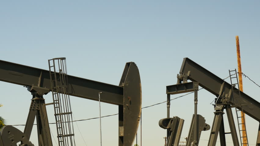 Working oil pump with blue sky in the background - 4K stock footage clip