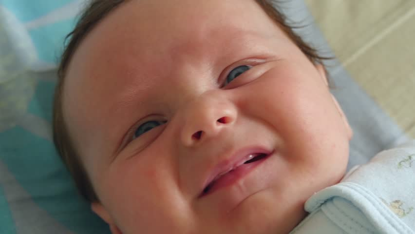 Portrait of a three months old baby boy on the bed in nursery room - 4K stock footage clip