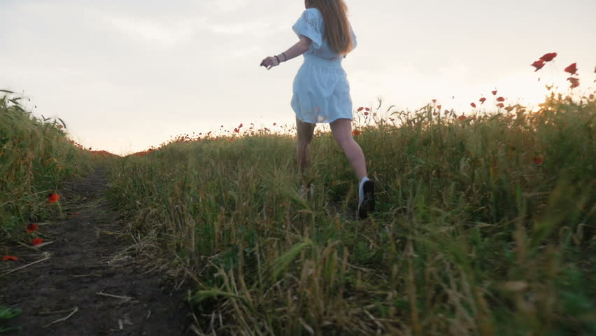 Young happy girl running in poppy field in white dress, slow motion - HD stock footage clip