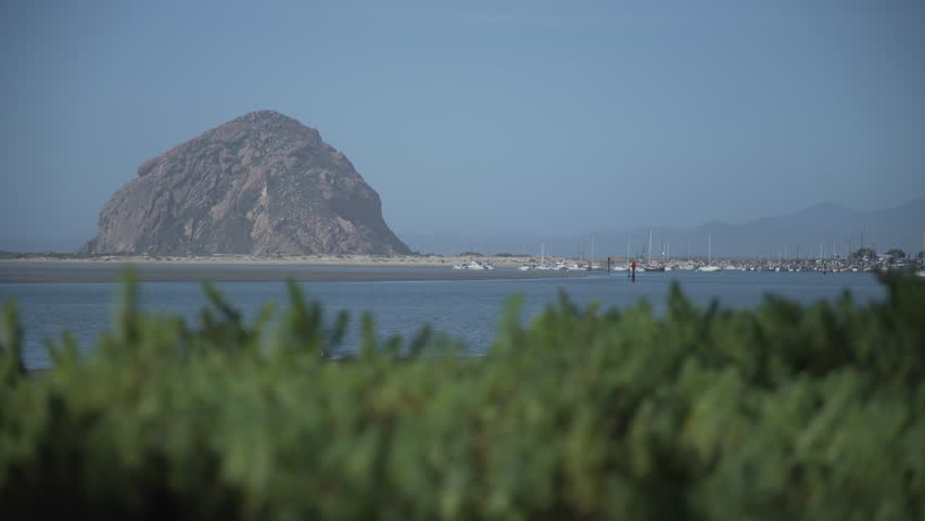 Morro Rock is a 581-foot volcanic plug located just offshore from Morro Bay, California, at the entrance to Morro Bay Harbor. A causeway connects it with the shore, effectively making it a tied island - 4K stock video clip