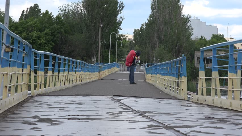 Traveling man with backpack standing on pontoon bridge across river at port