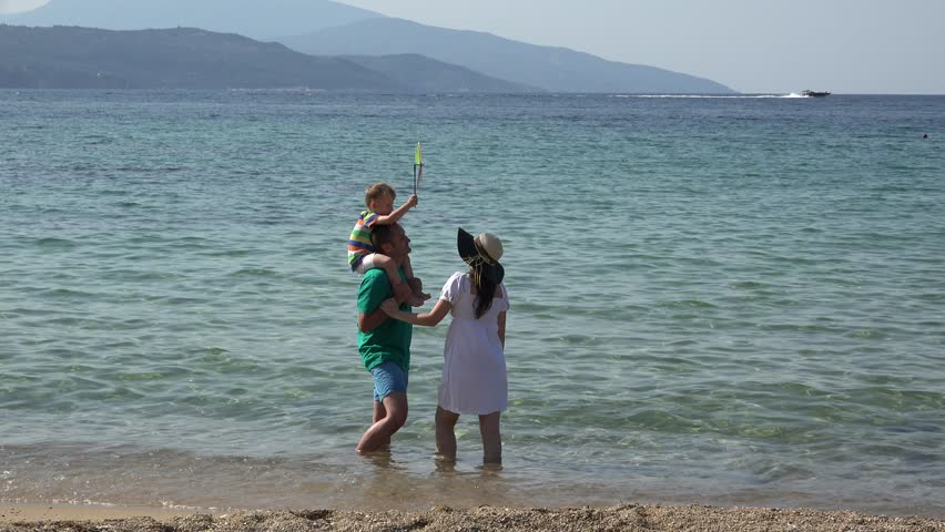 Young parents standing on seashore, father giving a piggyback ride to his son, child playing with pinwheel, blue sea in background - 4K stock footage clip