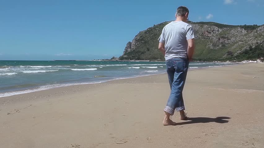 Middle-aged Caucasian man walking alone on the beach in a beautiful sunny spring day.