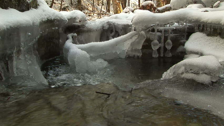 Water current pours into natural pool with ice formations - HD stock video clip