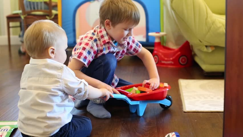 Two little boys play with toys on wooden floor in cozy room | Shutterstock HD Video #17244298