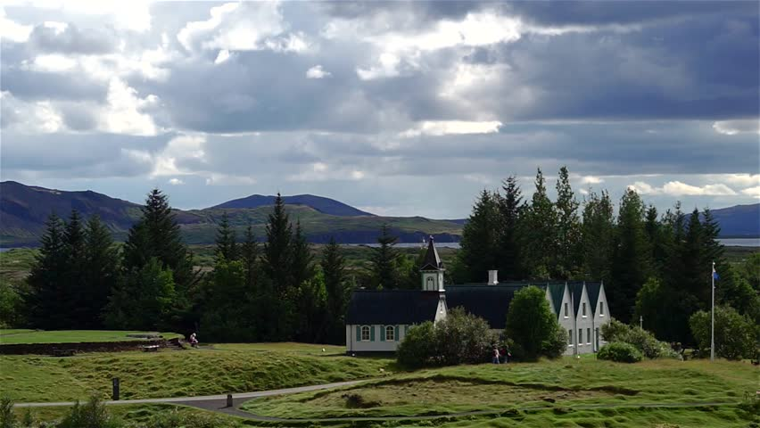 Dramatic shot of famous Pingvellir (Thingvellir) National Park, Iceland. Footage of white church in Pingvellir NP. Dramatic clouds over typical icelandic white church. - HD stock footage clip