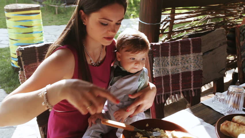 Mom feeding baby with spoon on nature | Shutterstock HD Video #17404228