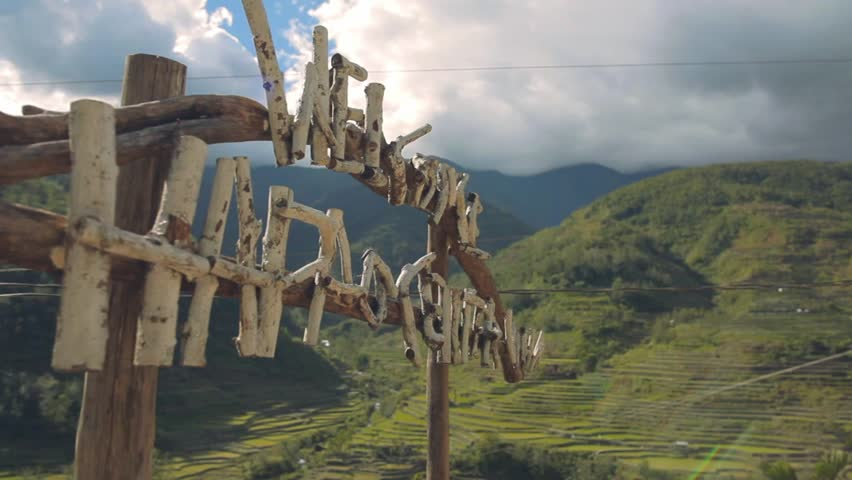 Breathtaking view of rice terraces and mountains during sunrise with close up on handmade Hapao Village sign near Batad, Ifugao, Philippines.