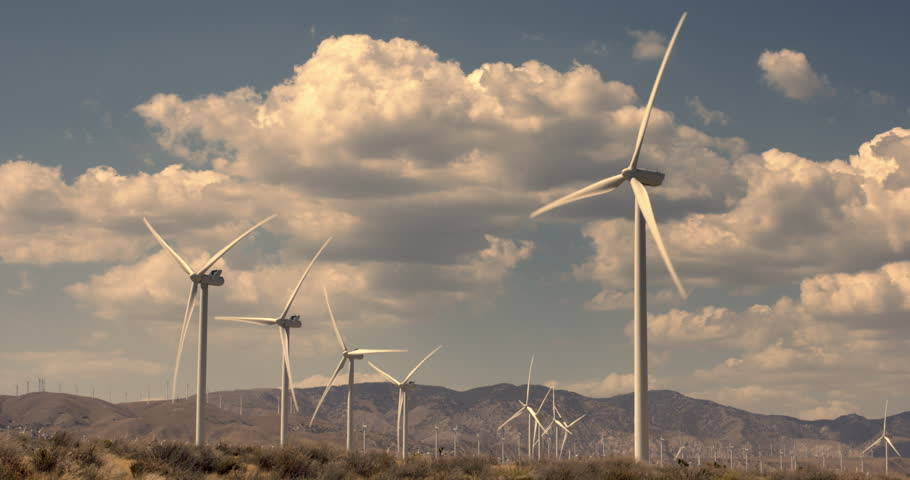 Wide view of large wind turbines tinted with golden light in Mojave Desert at Tehachapi in California.  Lots of puffy cumulus clouds and mountains visible in background. - 4K stock video clip