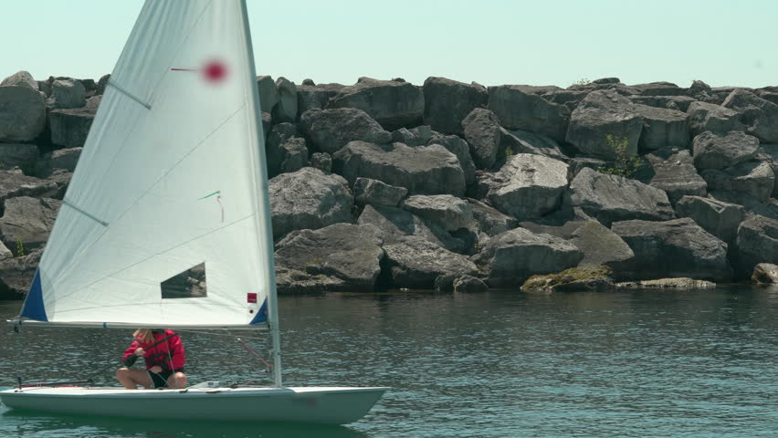 Racing dinghy. Single-handed racing dinghy going from sailing club out to the lake. This type of sailboat offers a huge amount of fun and family pleasure to all ages.  - 4K stock footage clip