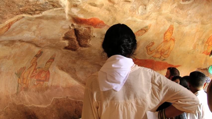 SIGIRIYA, SRI LANKA - OCTOBER 21, 2012: Unidentified people visit ancient paintings at the Sigiriya rock in Sigiriya, Sri Lanka. Sigiriya is a UNESCO World Heritage Site. - HD stock footage clip