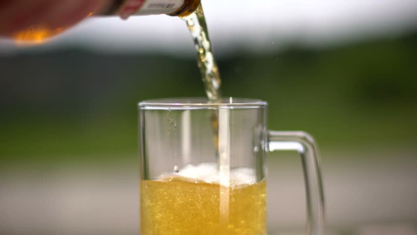 Locked down shot of pouring frozen beer inside a beer mug. - 4K stock footage clip