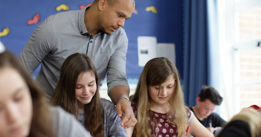 4k, A teacher helping his students with their work in the classroom. - 4K stock footage clip