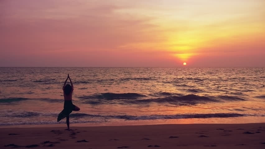 Young woman doing yoga (tree pose, asana, vrksasana) on a beautiful tropical beach at sunset.with ocean waves rolling in slow motion. Healthy lifestyle - fitness, slow motion peaceful. Graded look. - HD stock video clip