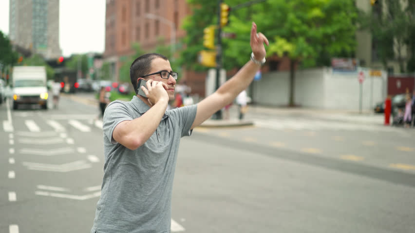 Young successful urban businessman with glasses talks on the phone and hail a yellow taxi cab in New York City standing on a busy Brooklyn street traveling to a startup company meeting | Shutterstock HD Video #17557534