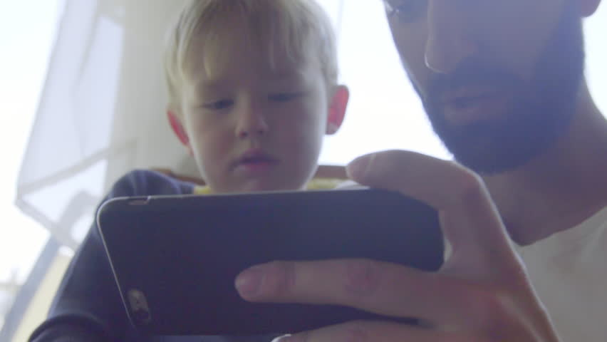 Close up shot of nephew and uncle playing games on a cell phone | Shutterstock HD Video #17583967