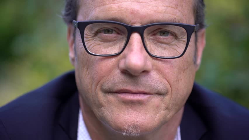 Portrait of a mature, attractive business man with black glasses looking at camera and smiling. #17586775