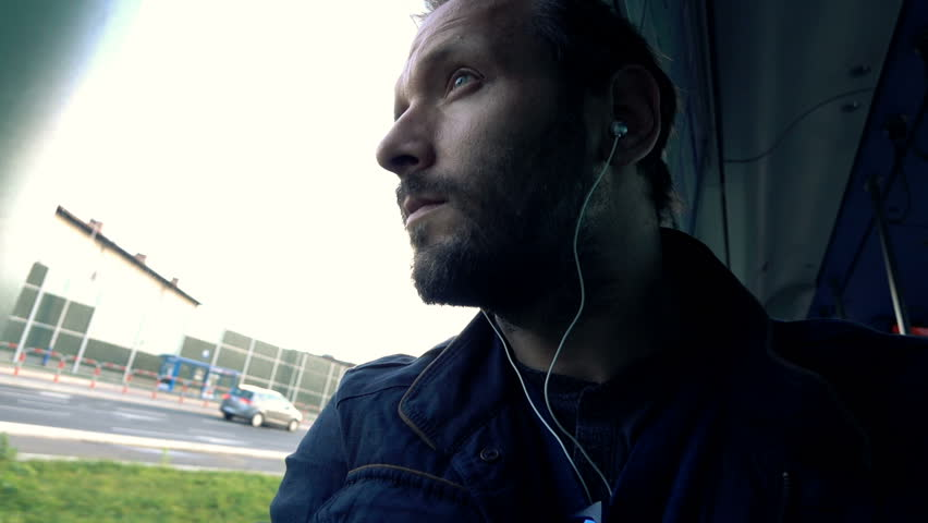 Pensive man listening to music during tram ride, super slow motion 120fps