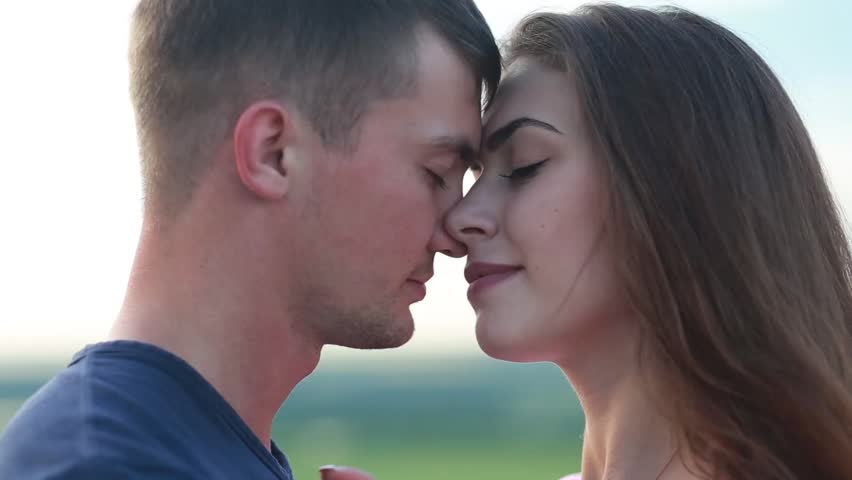 adorable young couple embracing and kissing tenderly in