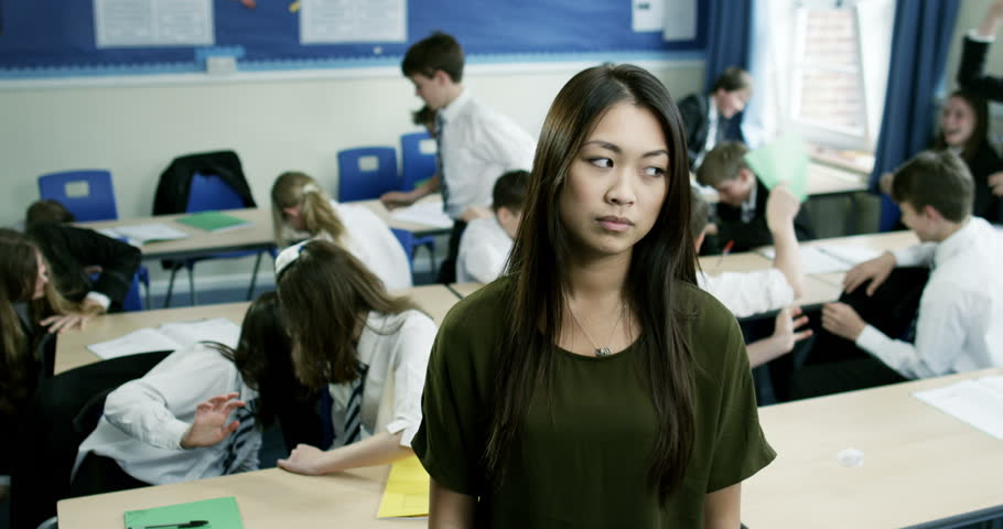 4k, Portrait of an unhappy class teacher while students wreak havoc in the background. Slow motion.