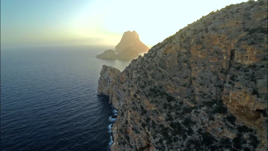 Aerial view of a cliff, in front of an islet named Es Vedra, at sunset, in the island of Ibiza.