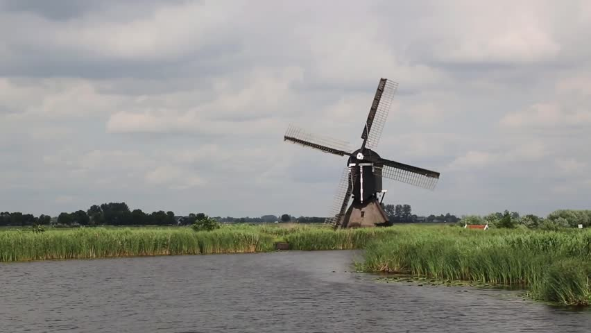 Turning Dutch windmill along canal in rural landscape, Streefkerk, South Holland, Netherlands - HD stock footage clip
