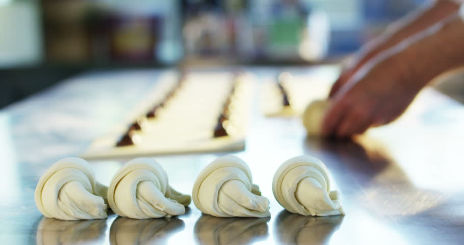 A hand of a chef prepares the croissants with chocolate stuffing and then they can be place in oven and serve to... #17774695