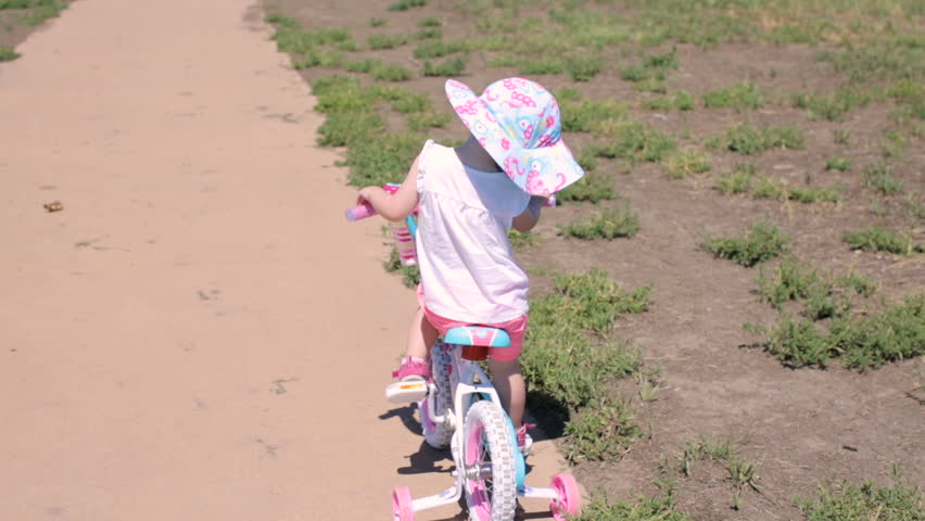 Toddler learning how to ride her first bike. | Shutterstock HD Video #17799364