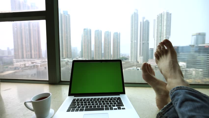 Amazing descending view of the skyscrapers from the high window, pretty workspace with laptop and morning cup of coffee and male feet in jeans. Hong Kong, China. | Shutterstock HD Video #17837038